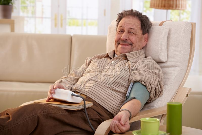 Äldre man som mäter blodtryck royaltyfria foton
