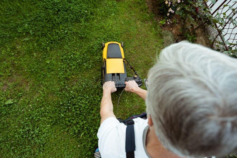 Äldre man som mejar gräsmattan royaltyfria bilder