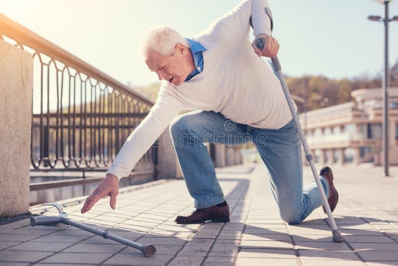 Äldre man som når för krycka, medan försöka att få upp royaltyfri foto