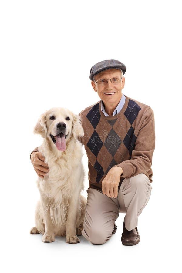 Äldre man som poserar med en hund arkivfoto