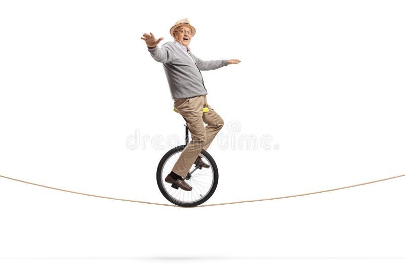Äldre man som rider en enhjuling på ett rep och balanserar med händer royaltyfri fotografi