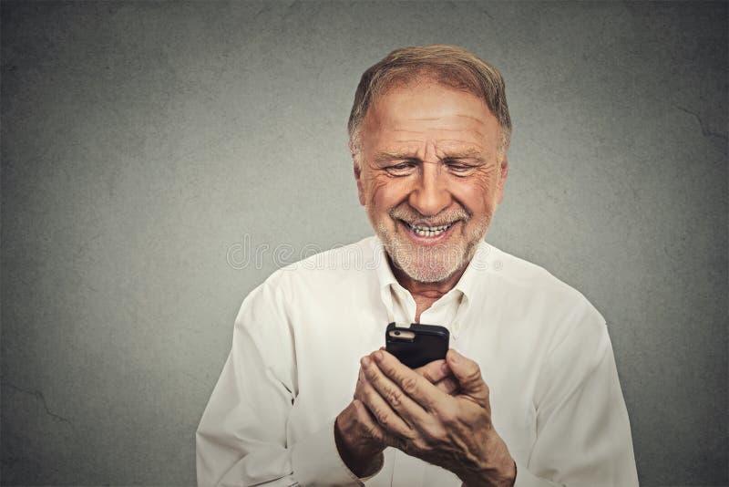 Äldre man som ser hans smarta telefon medan textmessaging arkivbilder