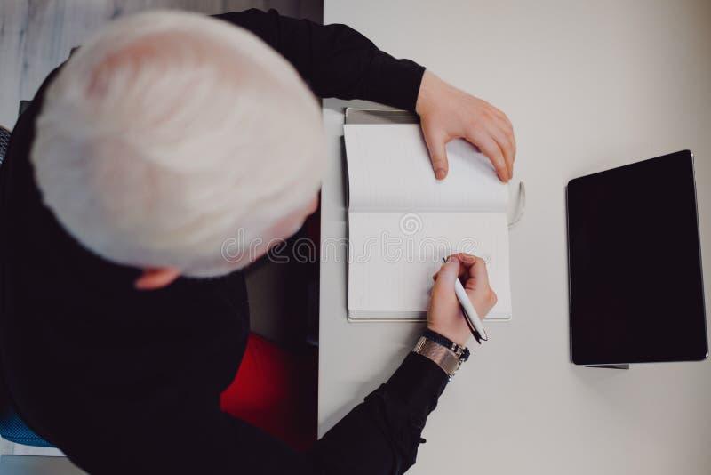 Äldre man som ser minnestavlan och skriver i hans anteckningsbok royaltyfri foto