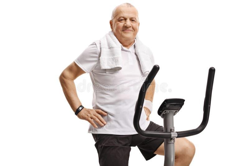 Äldre man som sitter på en motionscykel och ser kameran arkivfoto