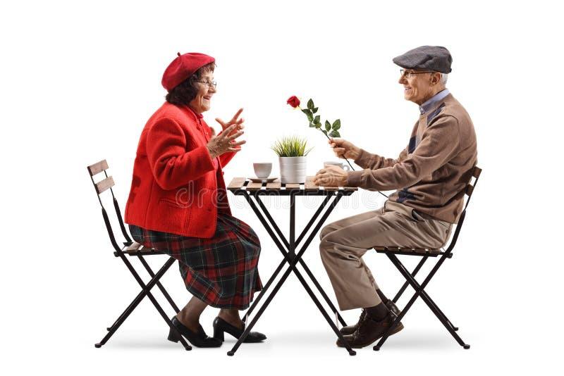 Äldre man som sitter på ett kafé och ger en röd ros till en äldre dam royaltyfri foto