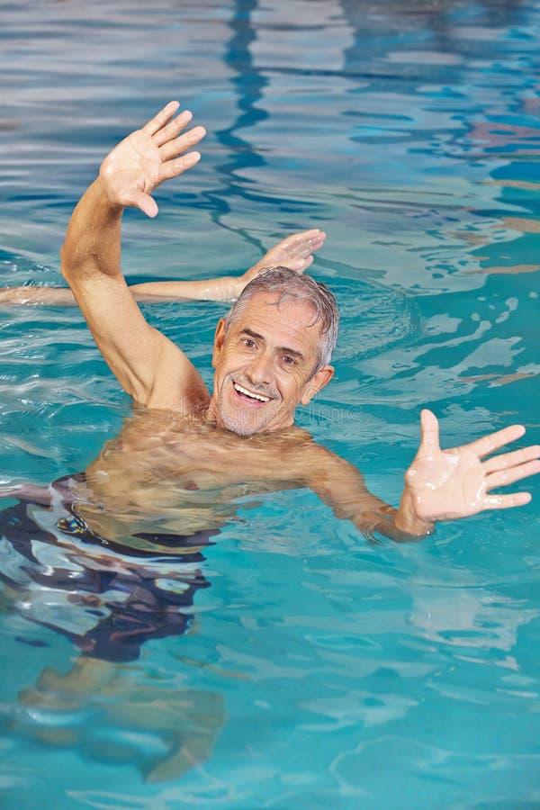 Äldre man som spelar vattenbollen i simbassäng royaltyfri fotografi