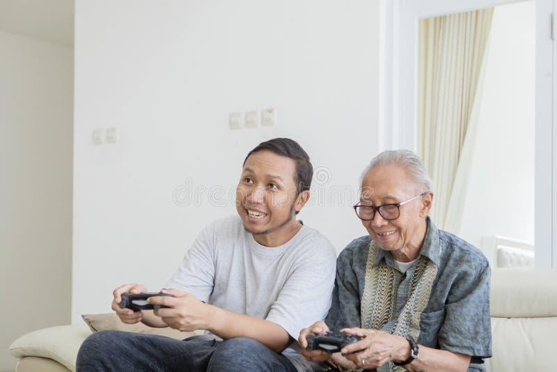 Äldre man som spelar videospel med hans son arkivfoto