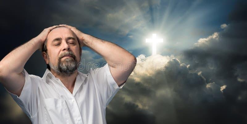 Äldre man som tänker om tro och gud arkivfoto