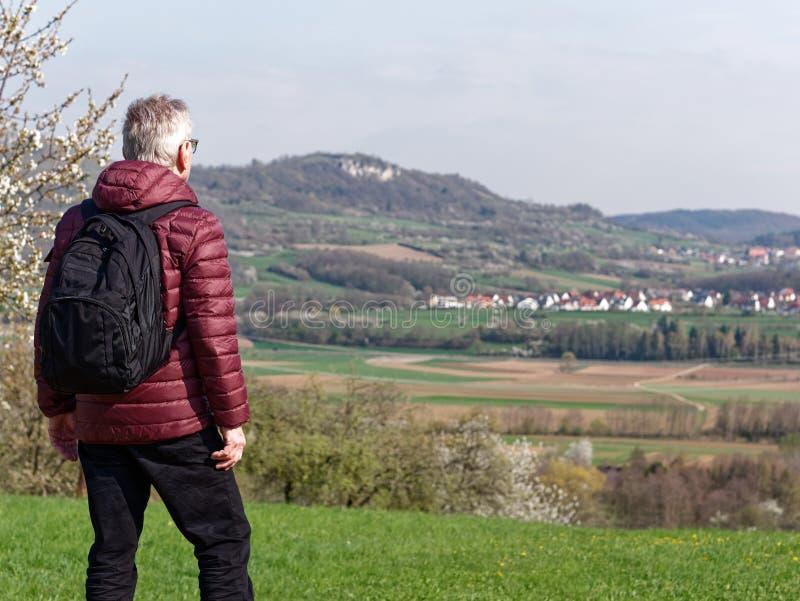 Äldre man som tycker om härligt landskap arkivbild