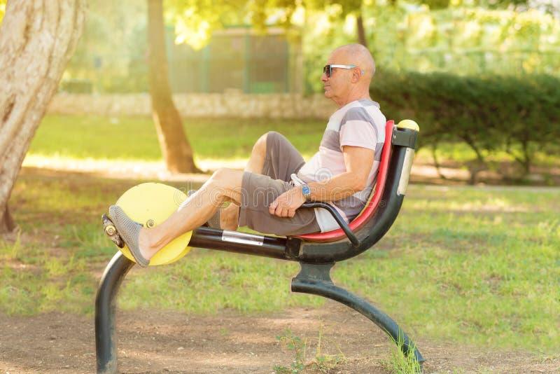 Äldre man som utarbetar på den offentliga utrustningen för sportar i den utomhus- idrottshallen royaltyfri fotografi