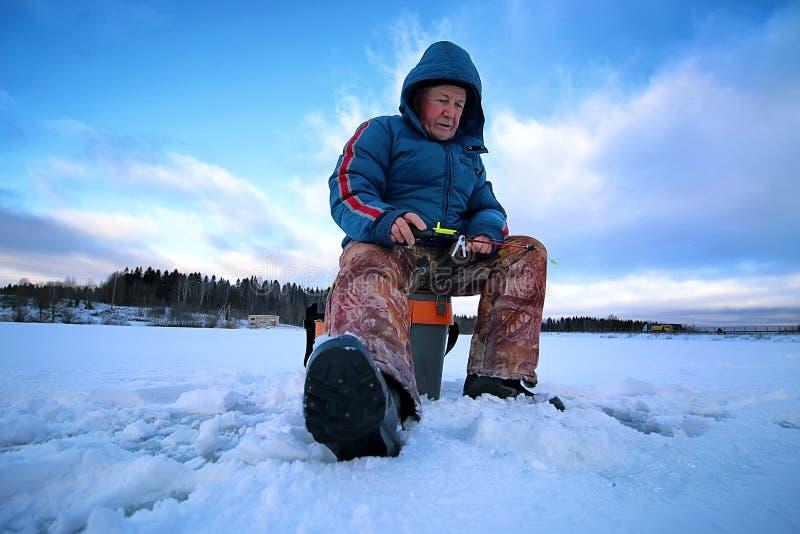 Äldre manfiske i vintern på sjön royaltyfri fotografi