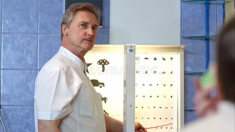 Äldre manlig ögonläkare som pekar på bokstäver av ögondiagrammet royaltyfria bilder