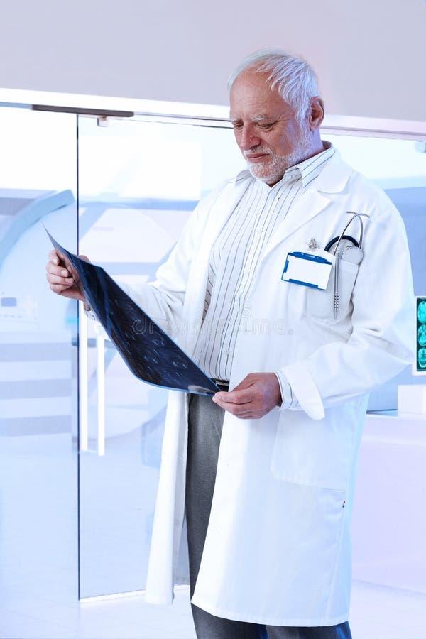 Äldre manlig doktor som kontrollerar bildläsning på sjukhuset fotografering för bildbyråer