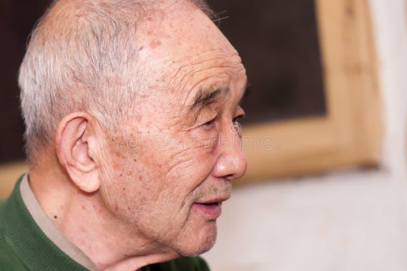 Äldre mans stående inomhus arkivfoto