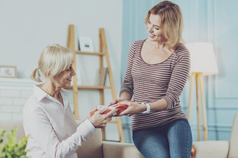 Äldre moder som mottar en gåva från hennes unga dotter arkivbild