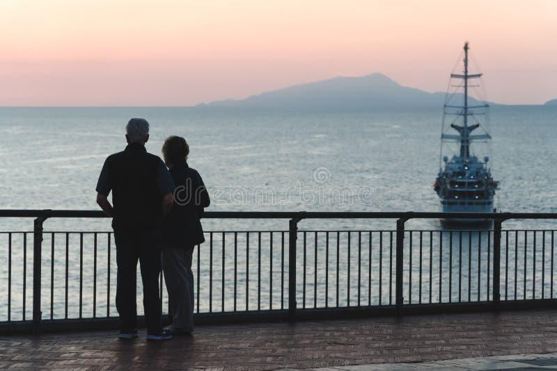 Äldre par för kontur som håller ögonen på solnedgången havshav, begrepp av pensionen och semester, lopp i stor haveyeliner för ga royaltyfria bilder