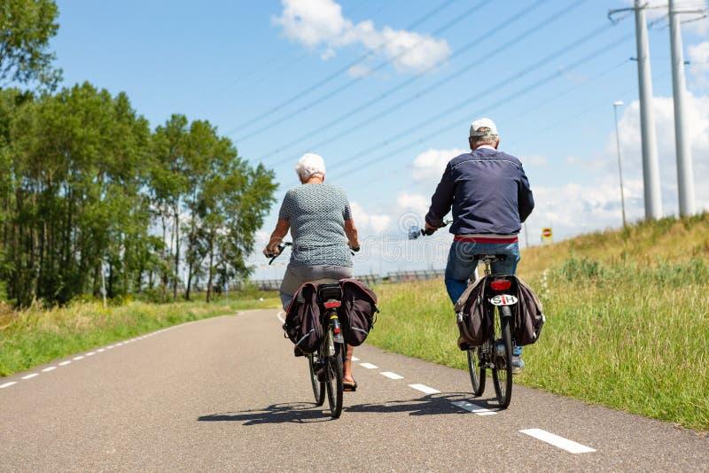 Äldre par som cyklar på asfaltvägen i Leiderdorp arkivbilder