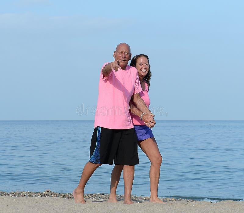 Äldre par som går stranden arkivbild