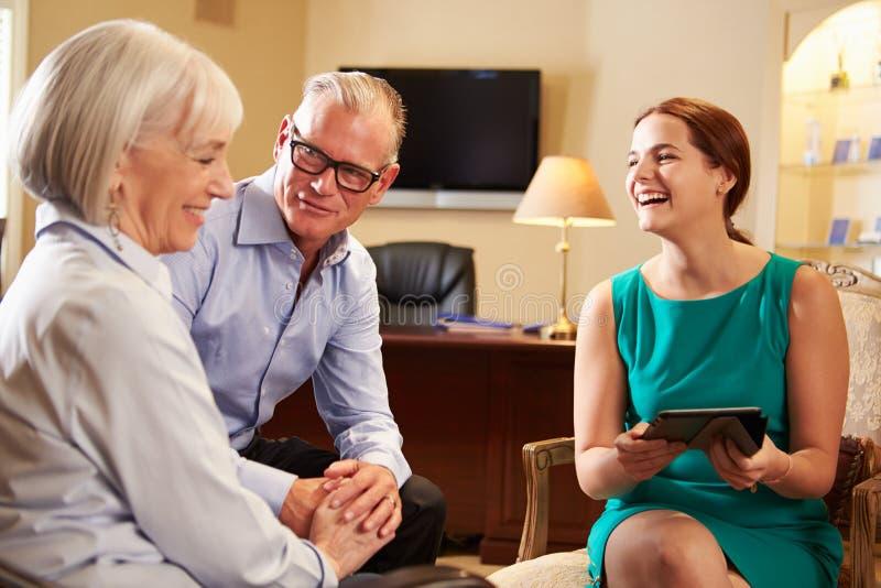 Äldre par som talar till den finansiella rådgivaren i Offic royaltyfri foto