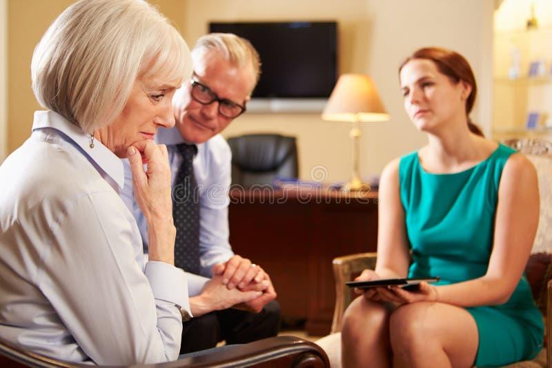 Äldre par som talar till rådgivaren som använder den Digital minnestavlan royaltyfri fotografi
