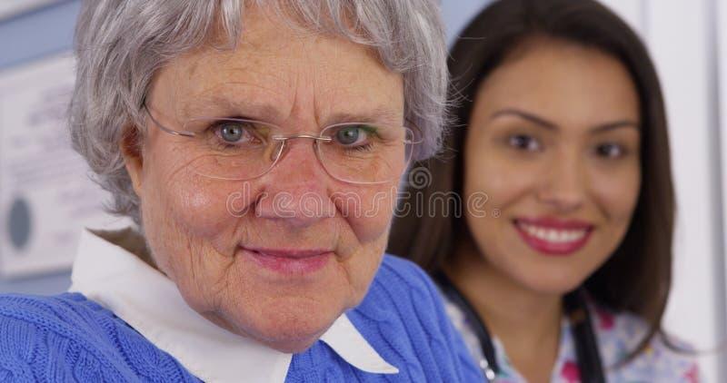 Äldre patient och mexikananhörigvårdare som ser kameran arkivbilder