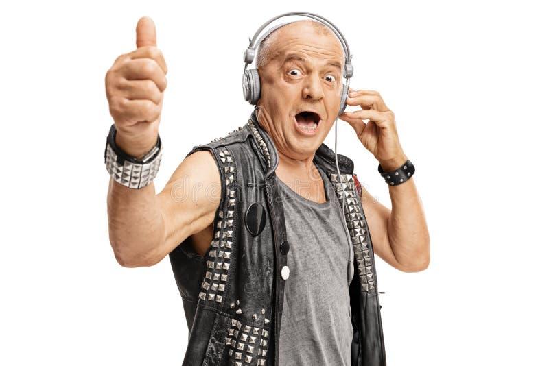 Äldre punker med hörlurar som rymmer upp hans tumme royaltyfri bild