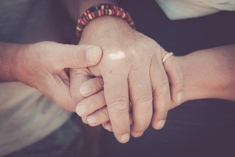 Äldre rörande pensionärhänder blir tillsammans royaltyfria foton