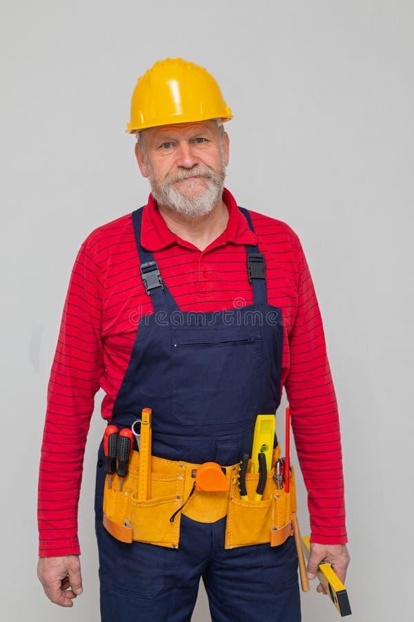 Äldre repairman som ser till kameran royaltyfria foton