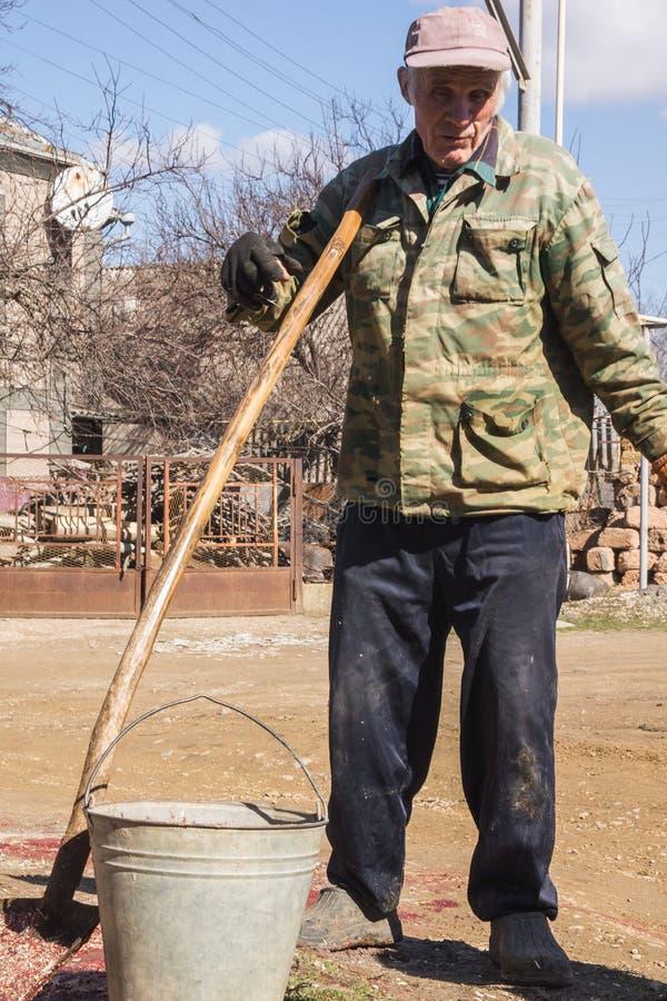 Äldre rysk bonde med skyffeln arkivbilder