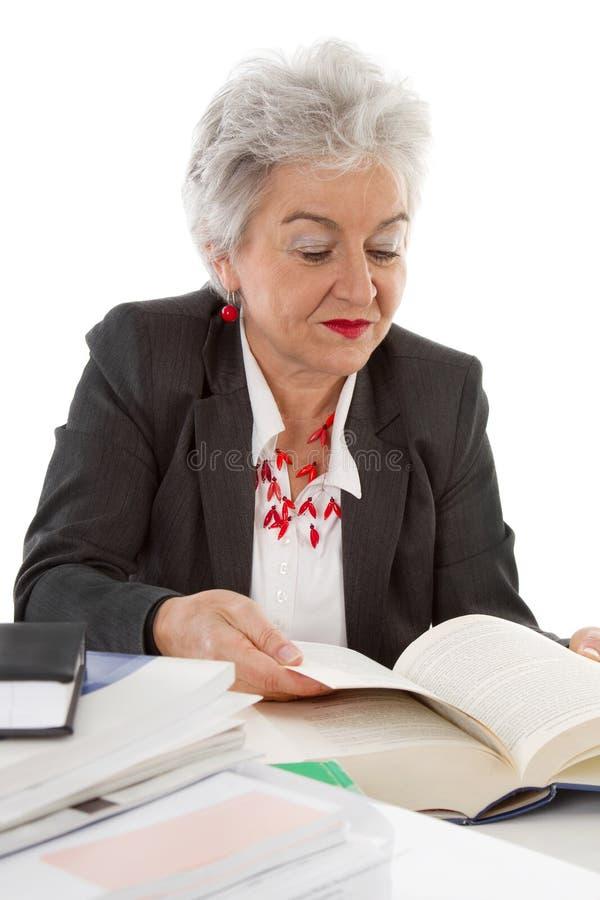 Äldre sammanträde för affärskvinna på skrivbordläsning i en bok Begrepp arkivfoton