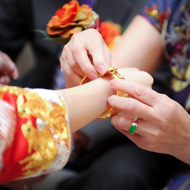 Äldre släktingar som framlägger det guld- armbandet arkivfoto