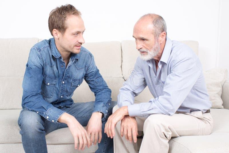 Äldre son som talar till hans fader royaltyfri bild