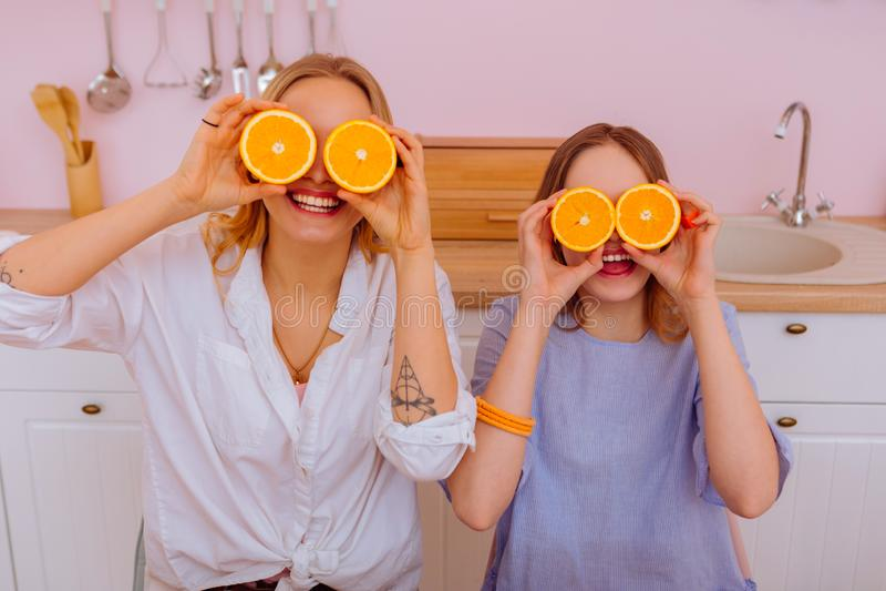 Äldre syster med tatueringen på hennes hand som rymmer apelsiner med hennes sibling arkivbild