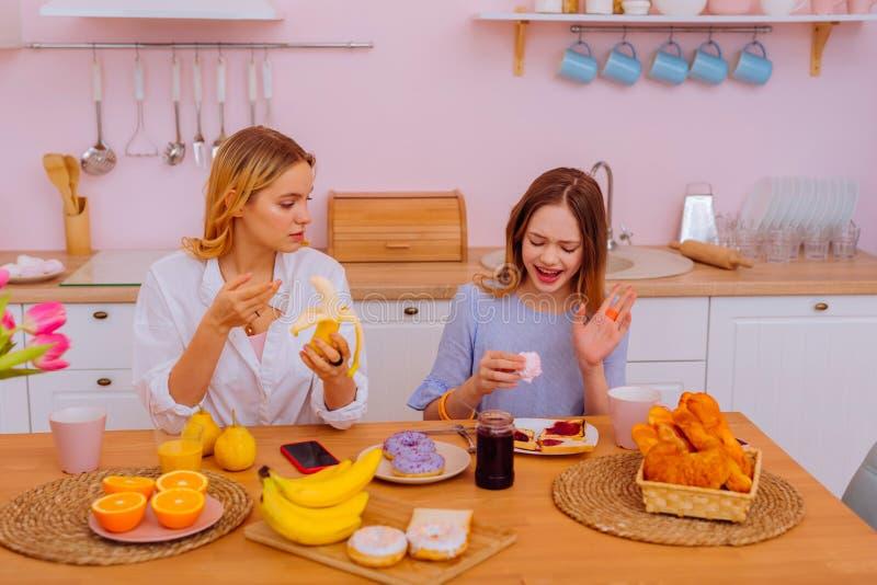 Äldre syster som äter bananen i morgonen nära hennes sibling royaltyfri foto