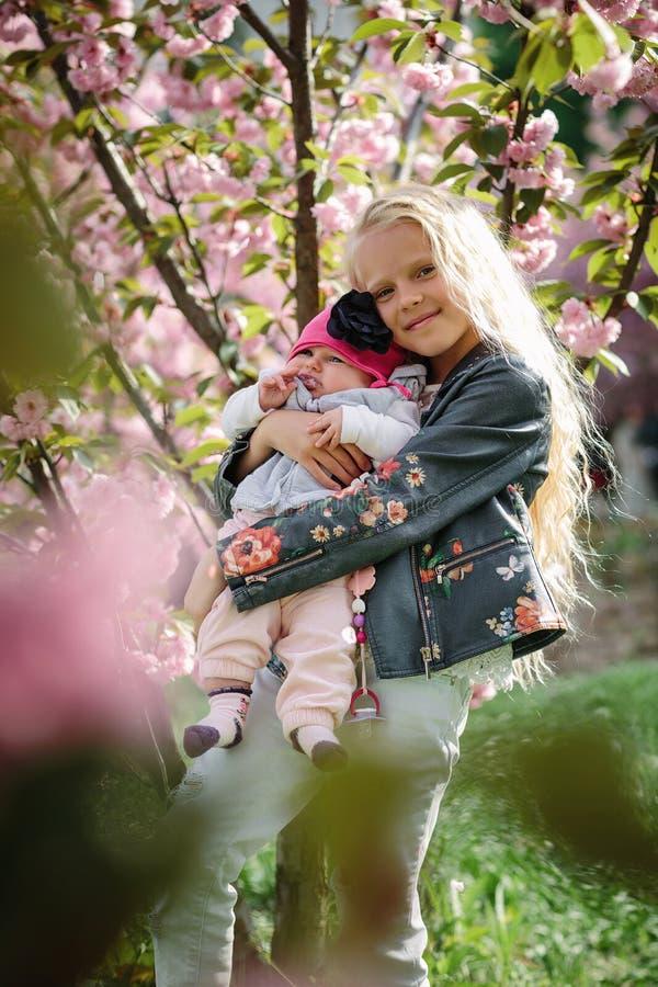 ?ldre syster som kramar den lilla systern royaltyfri fotografi