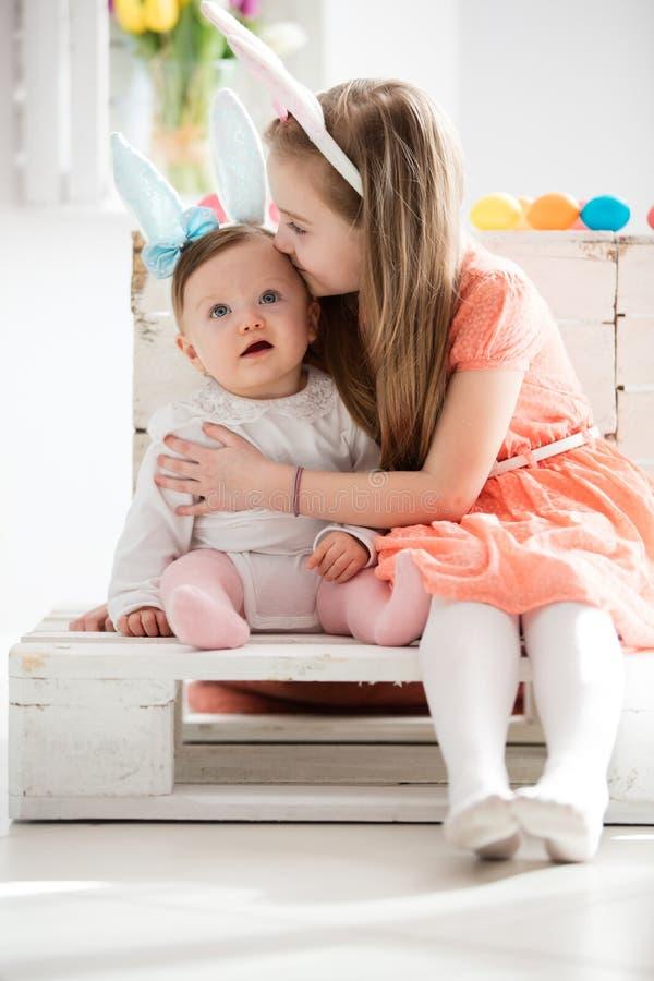 Äldre syster som kysser hennes mer unga sibling royaltyfri fotografi