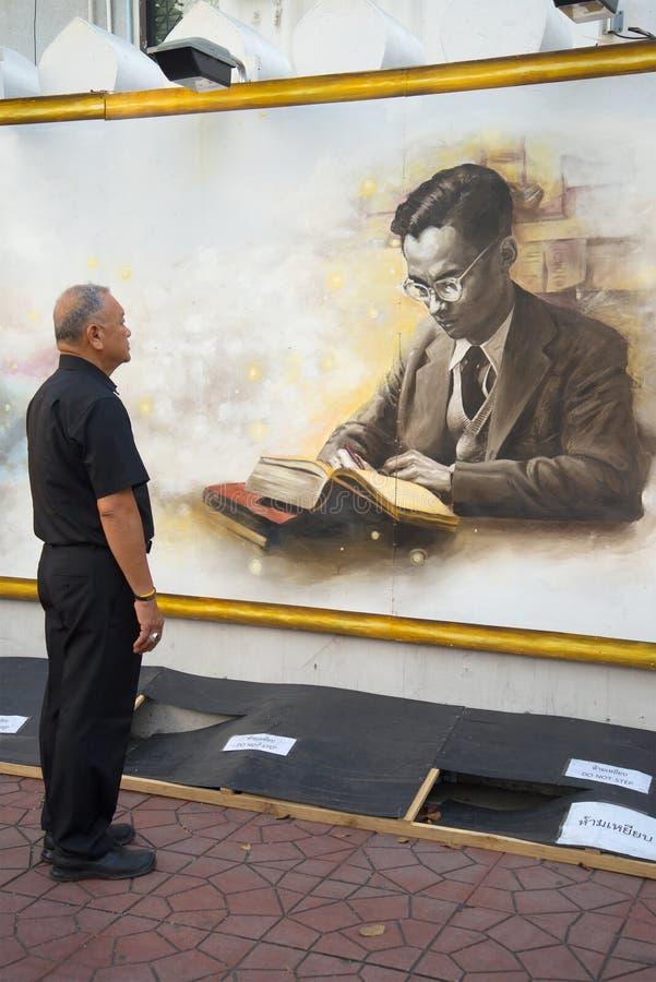 Äldre thailändskt i svart sorg beklär anseende nära väggen med bilden av konungen Bhumibol Adulyadej Bangkok arkivfoto