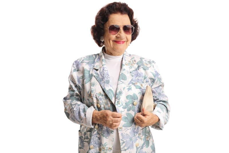 Äldre trendig dam med solglasögon och handväskan arkivbild