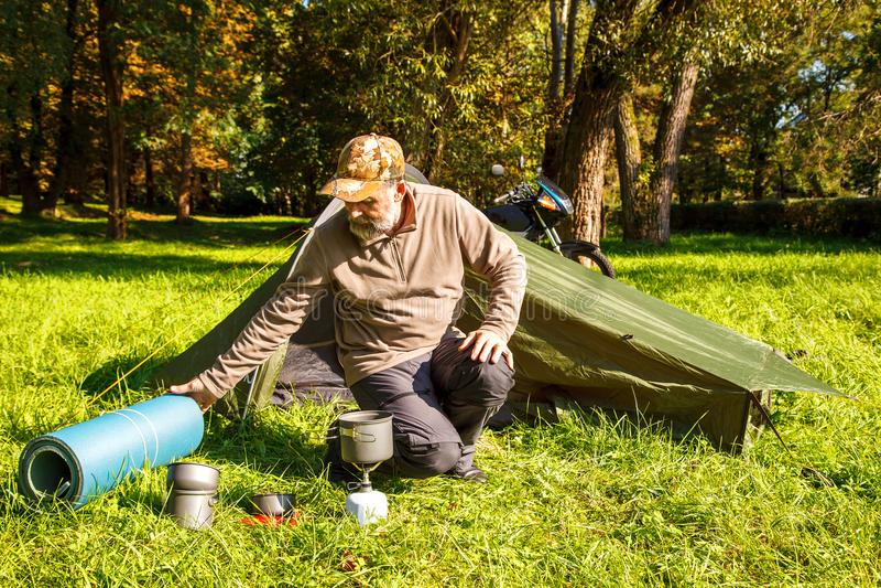 Äldre turist- foldjng ett tält i skogen arkivbilder