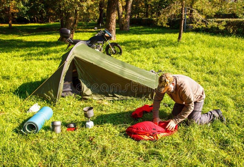 Äldre turist- foldjng ett tält i skogen fotografering för bildbyråer