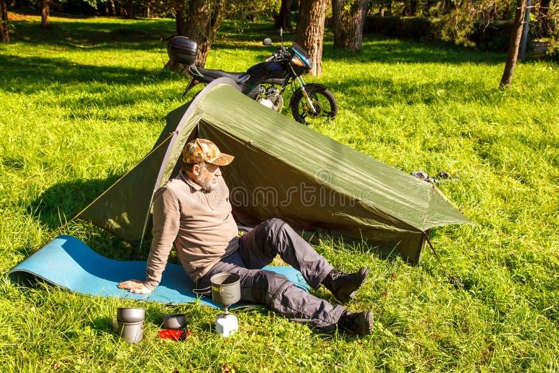 Äldre turist- vila sammanträde nära hans tält royaltyfri bild