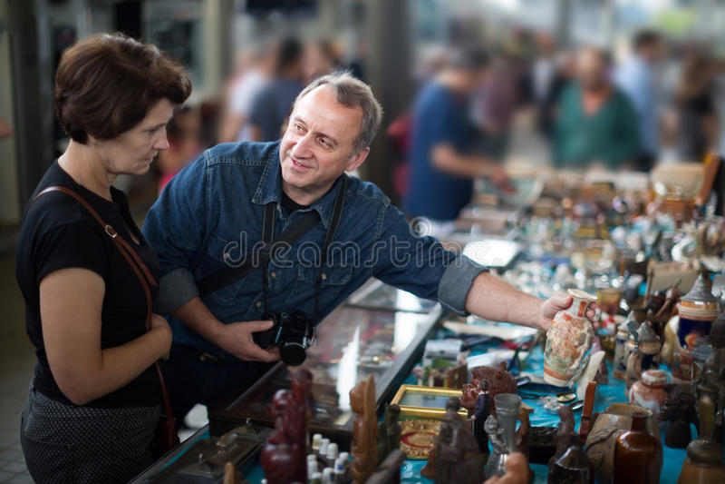 Äldre turister studerar området av loppmarknaden arkivbild