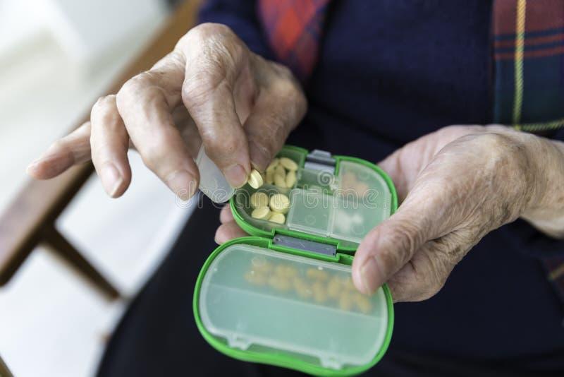 Äldre turkisk kvinna som tar preventivpillerar från asken arkivbild