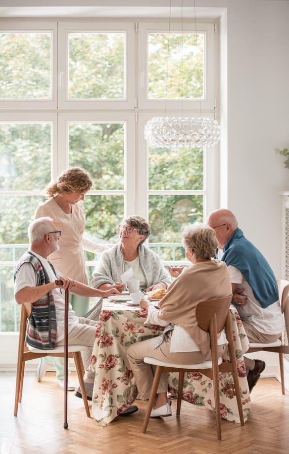 Äldre vänner som tillsammans spenderar tid, genom att dricka te och att tycka om foto i gemensam matsal av vårdhemmet arkivbild