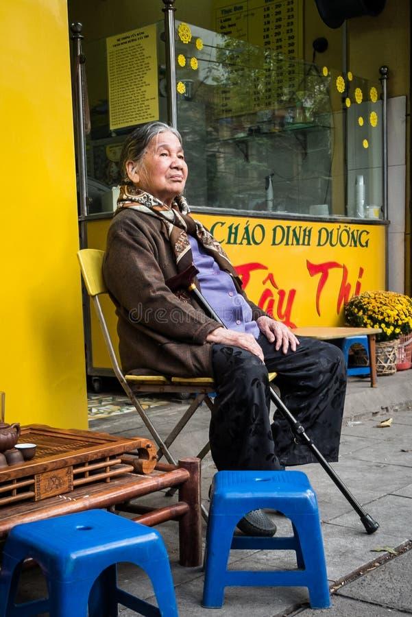 Äldre vietnamesiskt kvinnasammanträde i gatan royaltyfri foto