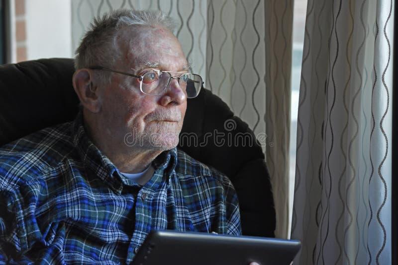 Äldre vuxen människa som ser ett fönster royaltyfri bild