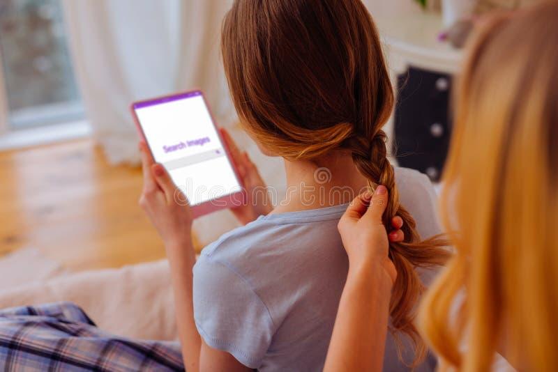 Älska äldre syster som gör den flätad tråden för hennes sibling som använder minnestavlan arkivfoton