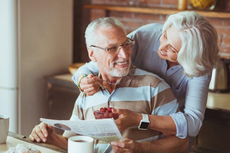 Älska åldrades par som tycker om deras frukost arkivfoto