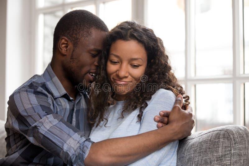 Älska afrikansk amerikanmaken som omfamnar frun efter, gräla arkivbilder