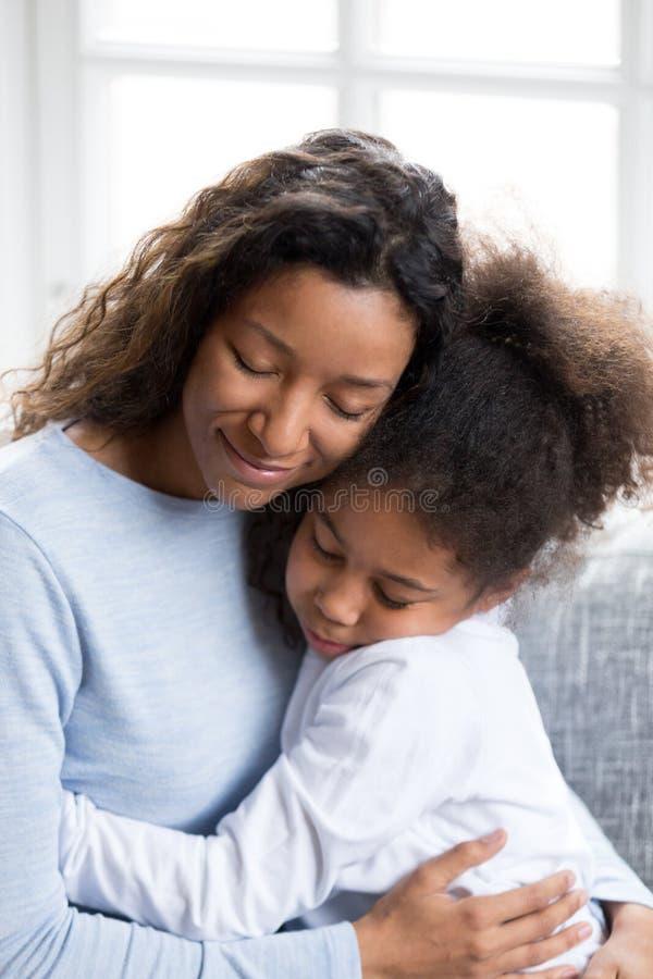 Älska afrikansk amerikanmodern som omfamnar med dottern arkivbilder